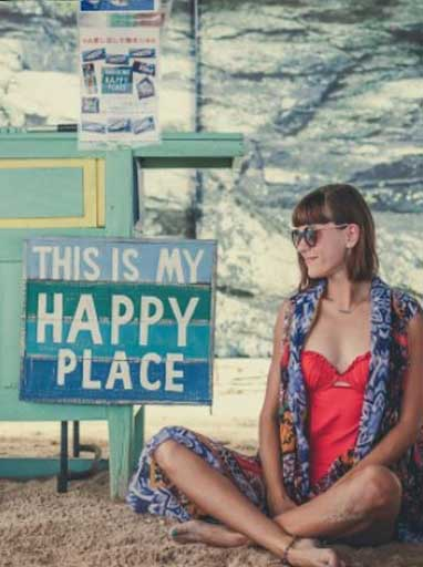 lady sitting on sand in front of sign