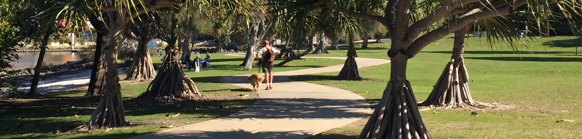 Man and his dog strolling along the meandering pedestrian pathway that travels between pandanus trees
