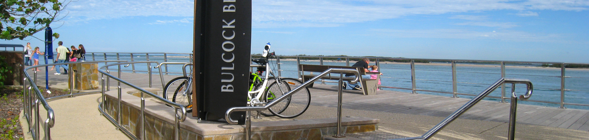Boardwalk overlooking the opal coloured water with the Bulcock Beach sign and parked bikes in the foreground